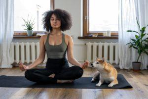 Woman with an afro meditating on a yoga mat beside an akita inu dog