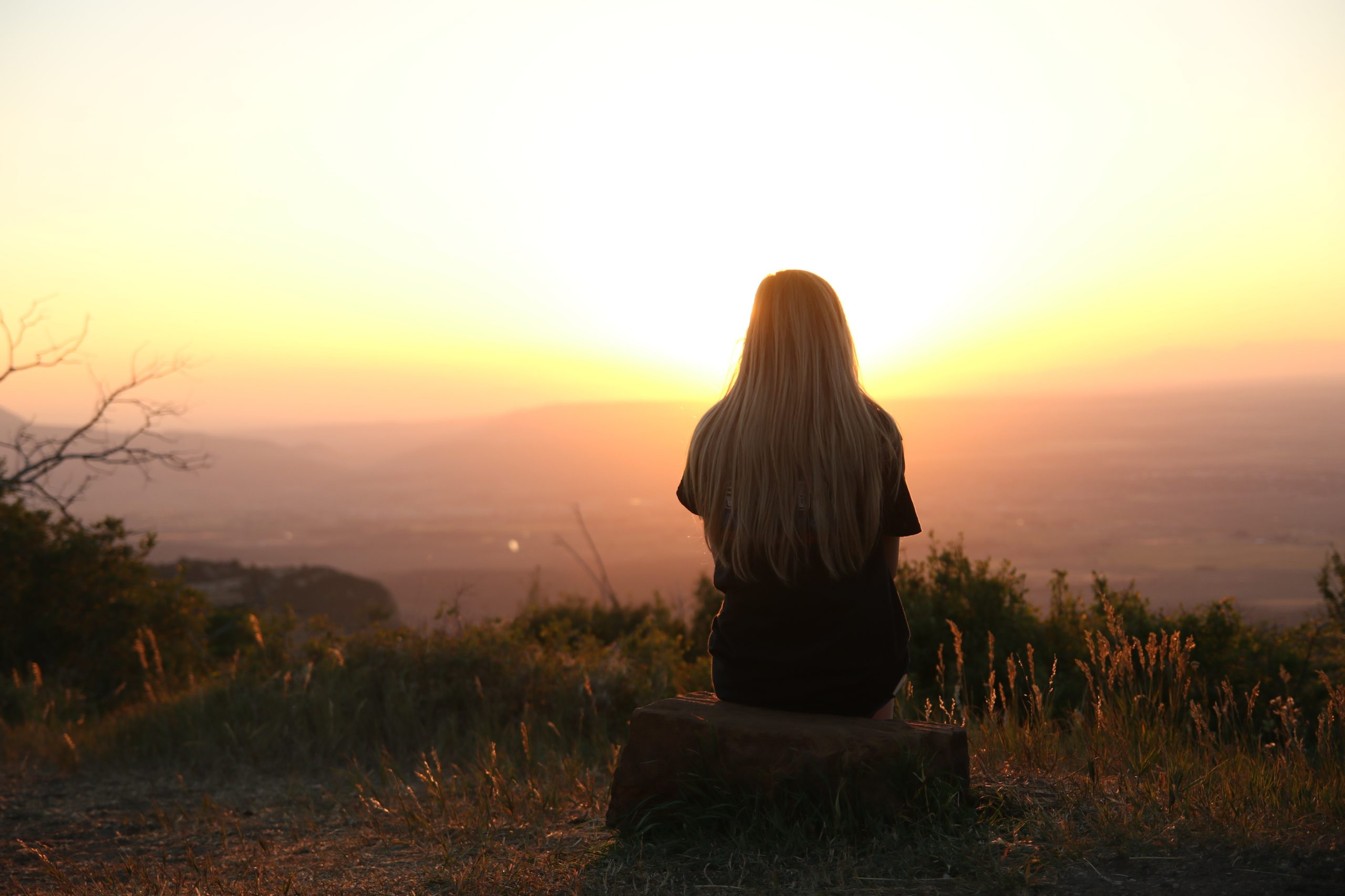 Girl sitting on a rock gazing out over the hills onto a sunset
