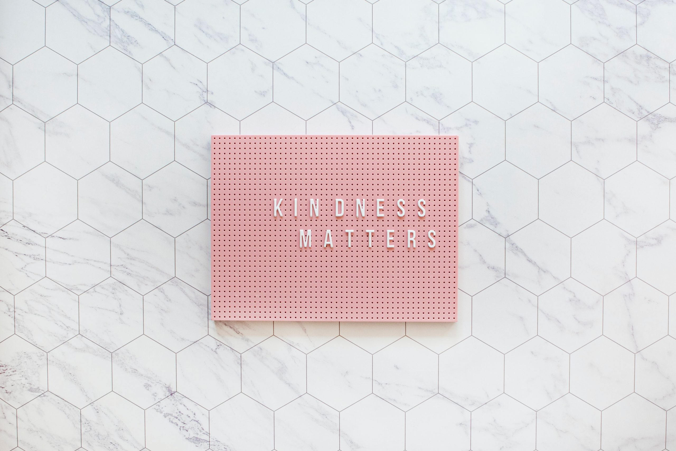Kindness matters written in all caps on a pink slate sat on a white marble background