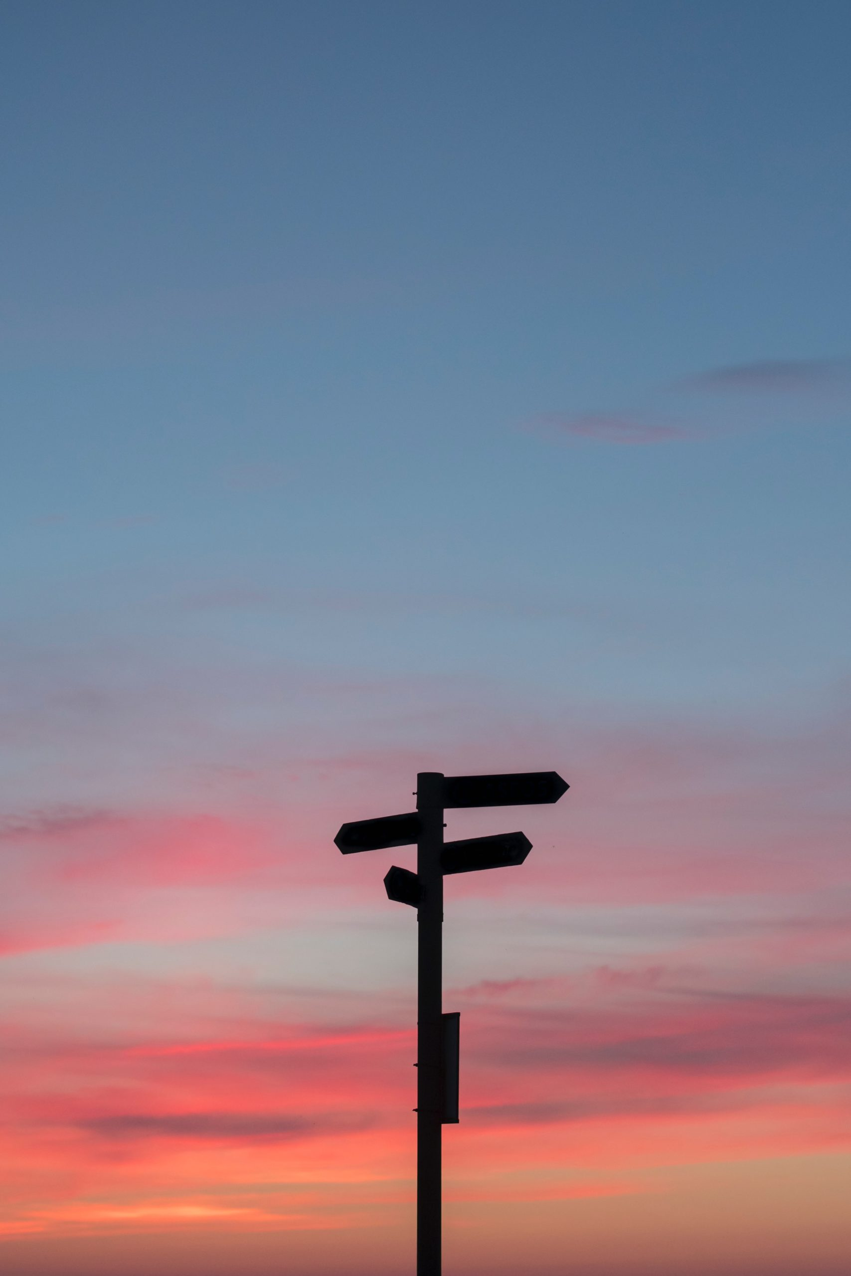 Signpost with signs pointing in multiple directions against a firey sunset sky backdrop