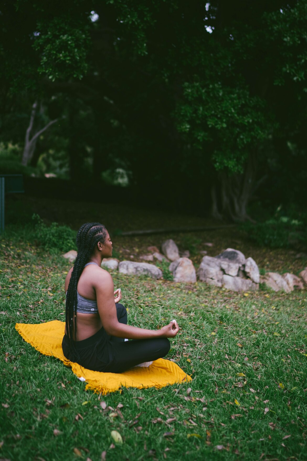 Black girl with box braids meditating outside on the grass, sat on a yellow blanket