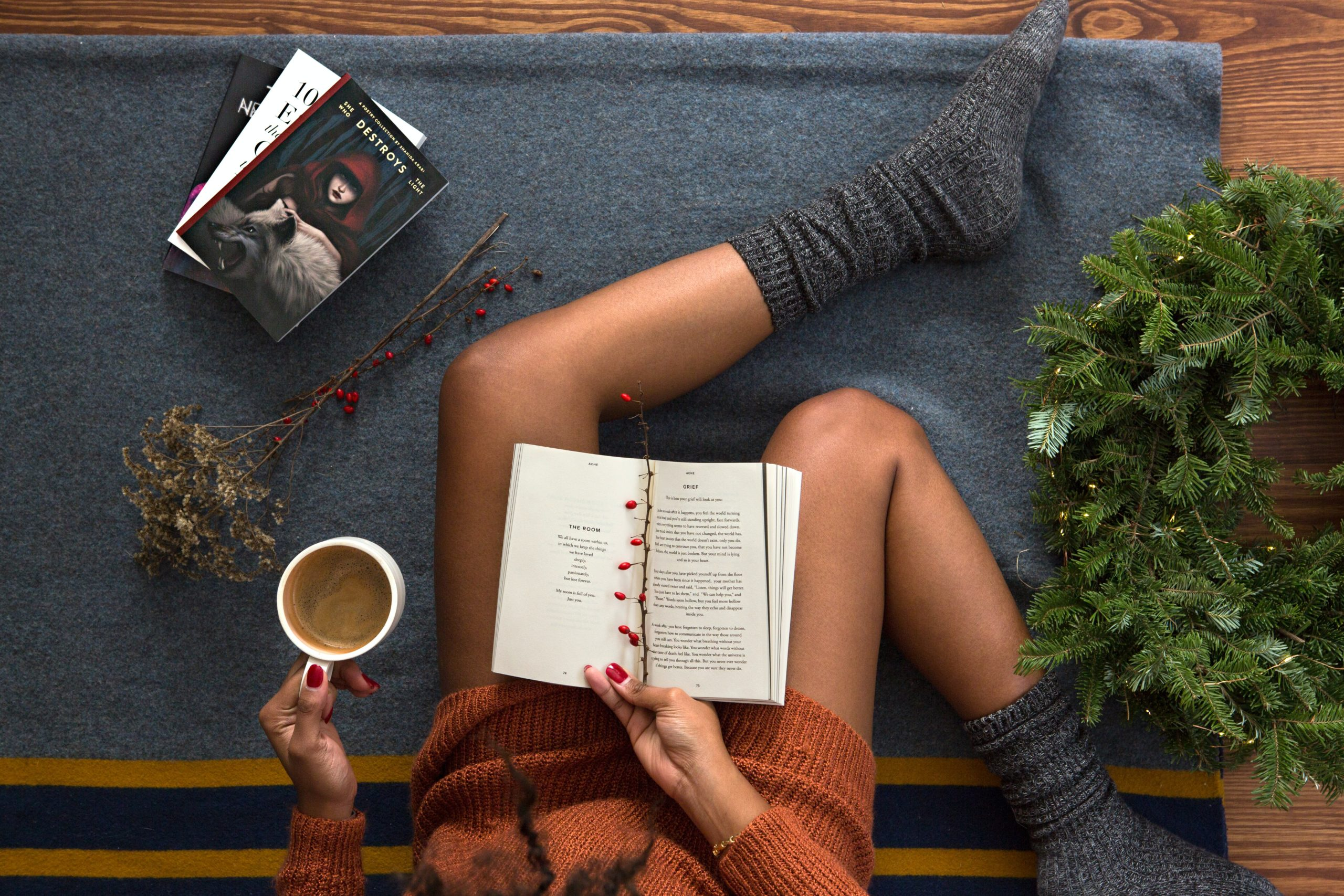 Woman in winter clothes reading a book with a mug of coffee